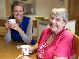 Community care worker joins an an elderly woman for a cup of tea while sitting at her kitchen table.