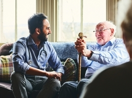 Young male doctor and senior man sitting on sofa and smiling during home visit