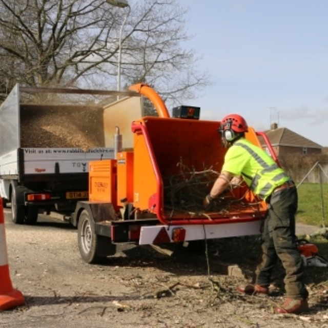 Member of commercial services team using a wood chipper