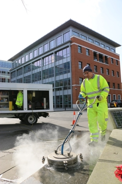 Commercial services team power washing pavement