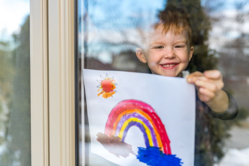 Child behind a window holding up a picture of a rainbow